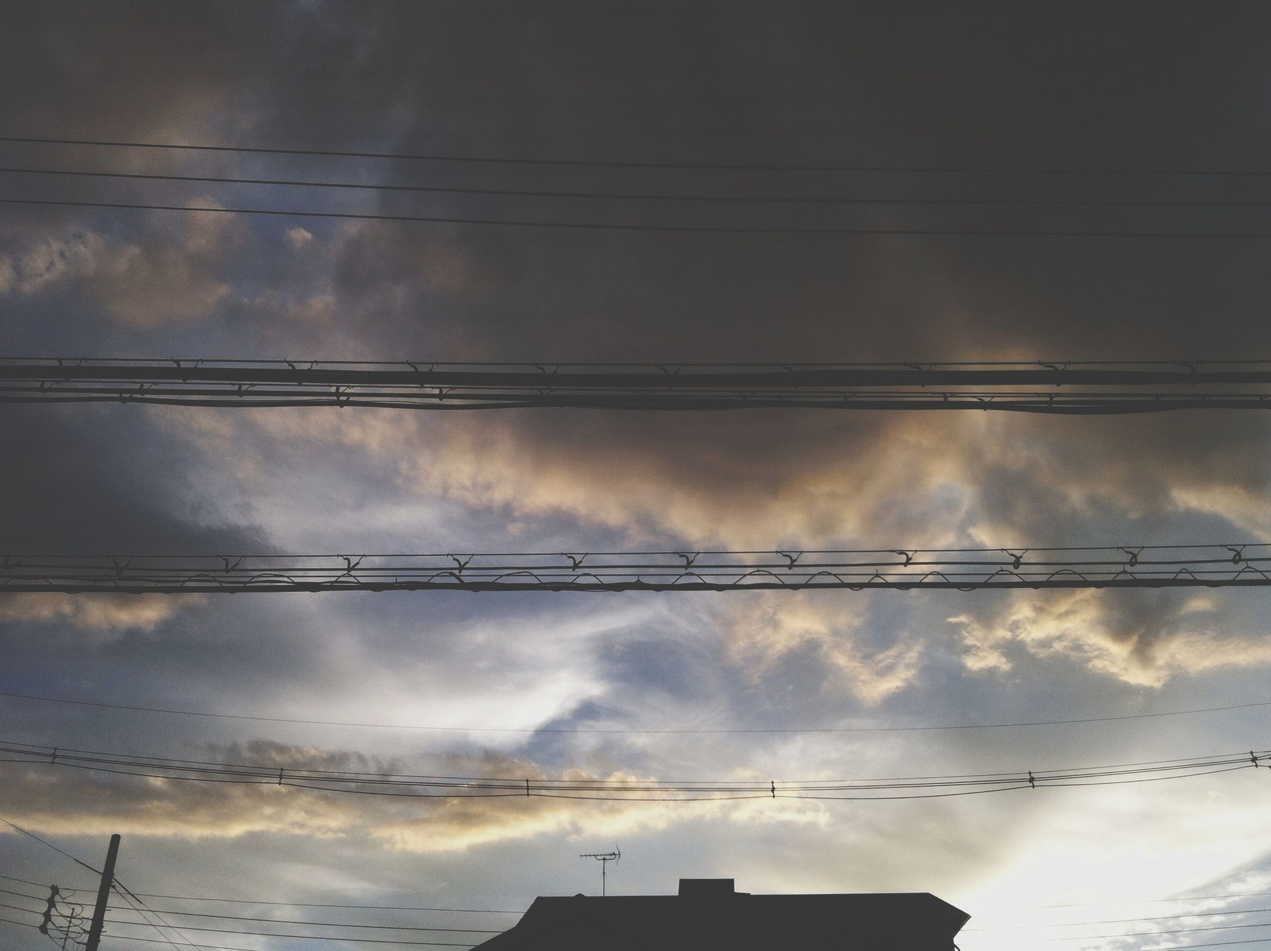 low angle view, sky, cloud - sky, power line, cloudy, built structure, architecture, cable, silhouette, building exterior, cloud, electricity, power supply, weather, connection, high section, electricity pylon, nature, outdoors, power cable