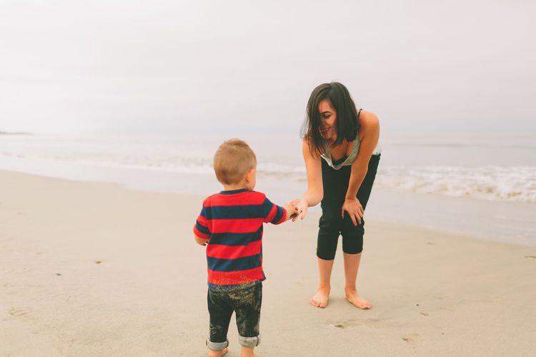 Mother and son standing at beach against sky