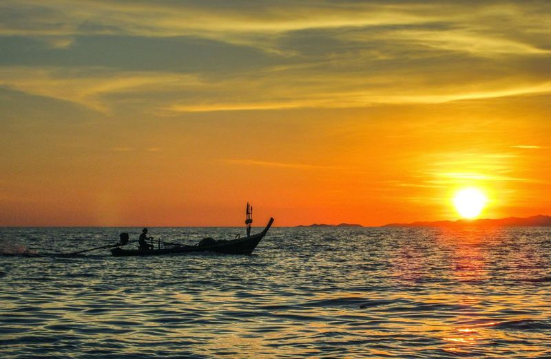 Silhouette of boat on sea at sunset