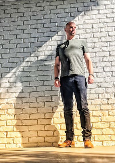 Full length of man standing against brick wall