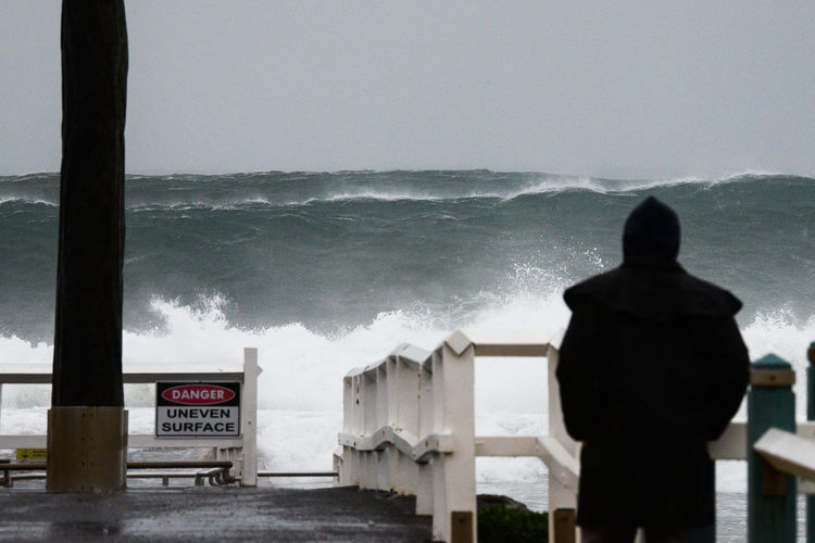 Rear view of person standing by railing against high tide