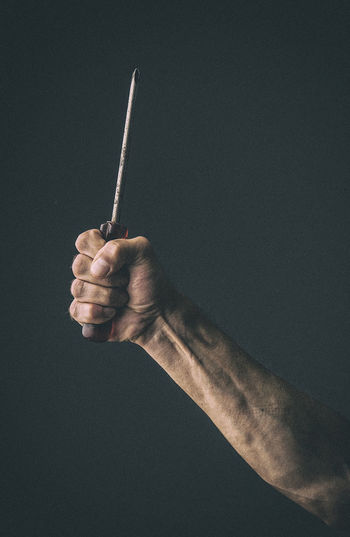 Close-up of person holding screwdriver against black background