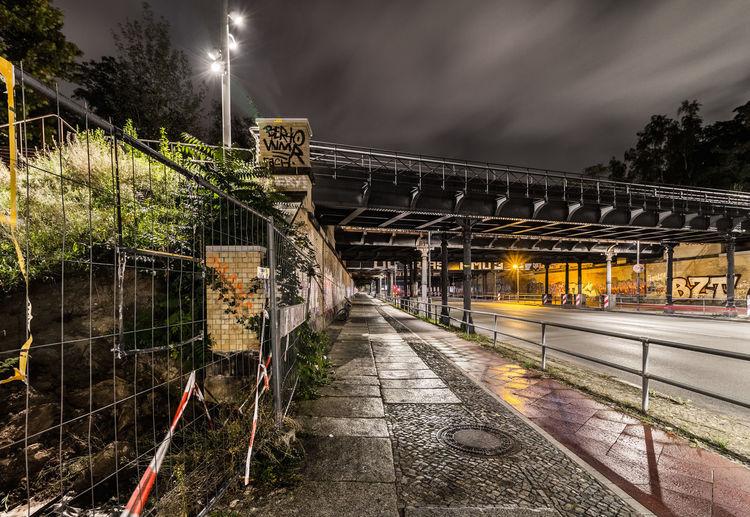 Illuminated railroad tracks by street against sky at night