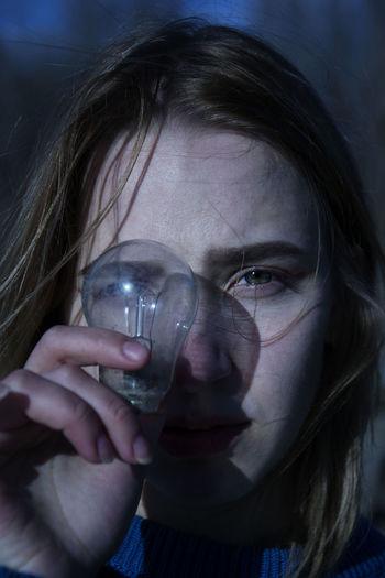 Close-up portrait of beautiful woman holding light bulb