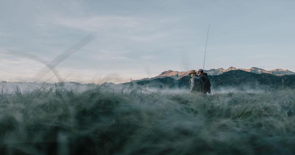 Man standing on field against sky flyfishing