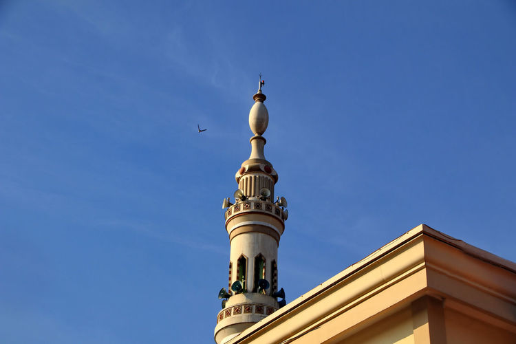 Low angle view of mosque building against blue sky