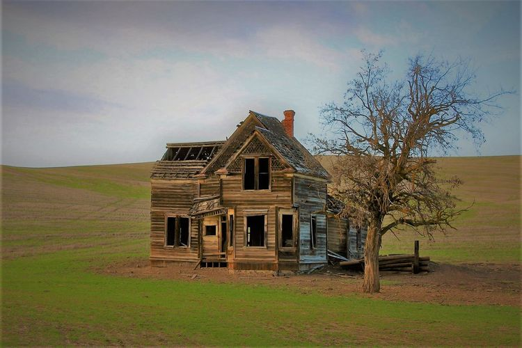 Abandoned house in field against sky
