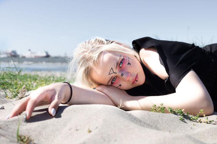 Portrait of young woman lying on beach against sky