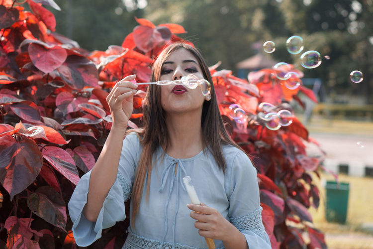 Beautiful young woman blowing bubbles while standing against plants