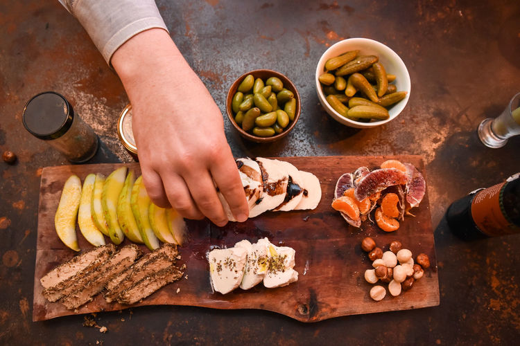 Top down view of Appetizer Platter Appetizer Appetizers Apple Body Bread Cheese Platter Eating Food Fruit Grabbing Food Grape Fruit Hand Nuts & Seeds Pickles Platter Stock Photo Tree Fruit Wine. Top Down Food And Drink Human Hand One Person Healthy Eating Cutting Board High Angle View Snack