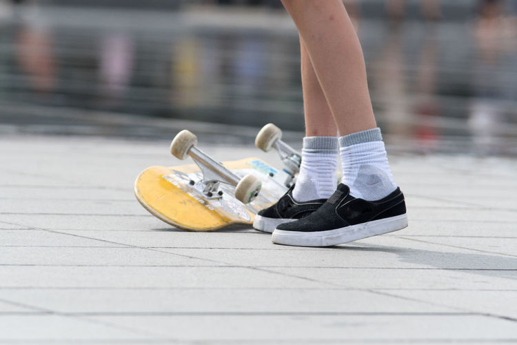 Low Section Of Man With Skateboard Standing At Skateboard Park