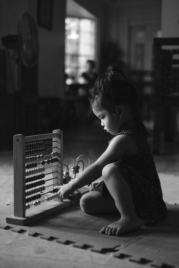 Side view of girl playing at home