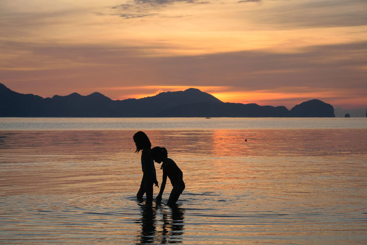 Silhouette Girls Walking In Sea Against Sky During Sunset