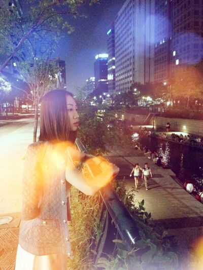 Real People City Night Lifestyles One Person Building Exterior Illuminated Holding Leisure Activity Standing Outdoors Women Happiness City Life Young Adult Tree Beautiful Woman Architecture Sky Adult Gallery Film Art Artstagram Selfie