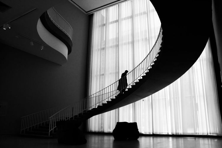 Low angle view of person standing on staircase in building