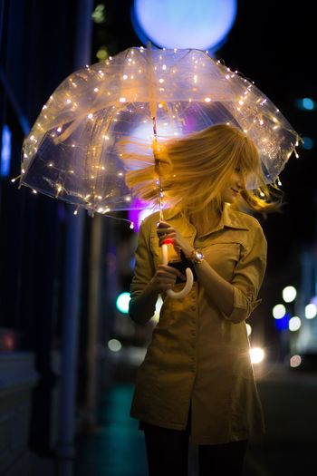 Woman tossing hair while standing with illuminated umbrella in city at night