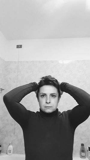 Portrait of serious woman with hands behind head standing in bathroom