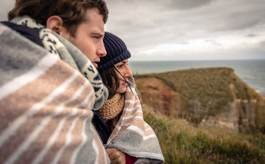 Couple Covered With Blanket Looking At Sea