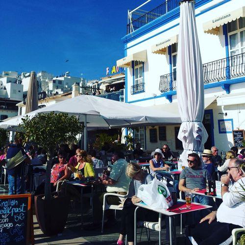新年のカウントダウンを待つ人々でレストランは混んでいます。ビールやサングリア片手にゆっくりおしゃべりに興じています。 Eating People Outdoors Adult Men Women Sea And Sky Blue Happy Life Enjoying Life Quality Time Building Exterior Clear Sky Travel Destinations Vacations Restaurante Cafe