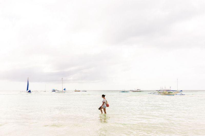 Woman Walking On Shore Against Sky At Beach