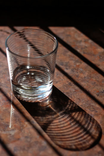 Glass reflection. Dark Shadow Sunlight Close-up Dark Drinking Glass Drinking Water Food And Drink Glass Glass - Material High Angle View Household Equipment Indoors  Kitchen Kitchen Worktop Nature No People Refreshment Relection Selective Focus Shadow Shot Glass Table Water Wood - Material