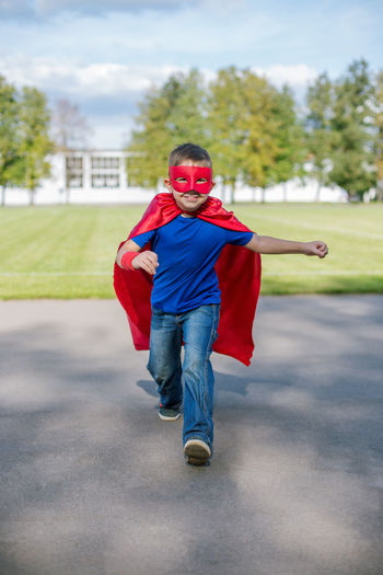 Full length of boy in superman costume walking on road against sky