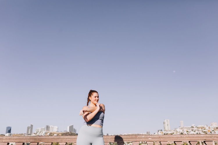 Woman standing by cityscape against clear sky