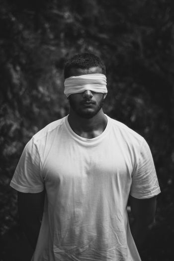Man with blindfold standing outdoors