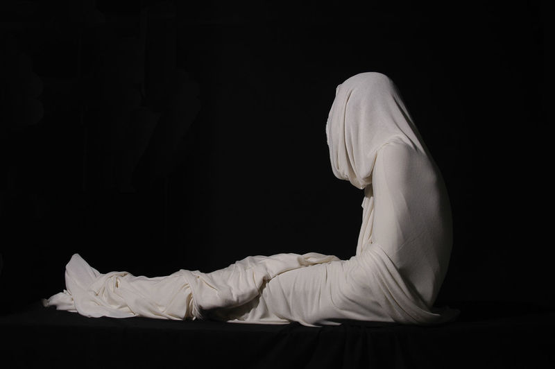 Person wrapped in fabric while sitting against black background
