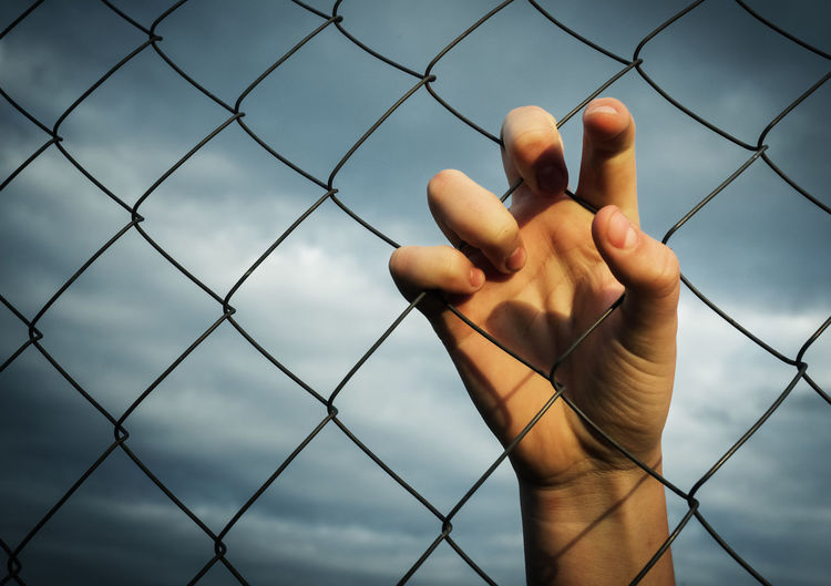 Cropped image of hand holding chainlink fence against cloudy sky