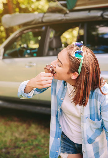 Young Woman Eating Ice Cream Cone While Standing Against Car