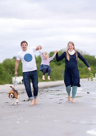 Full length of happy family walking at beach