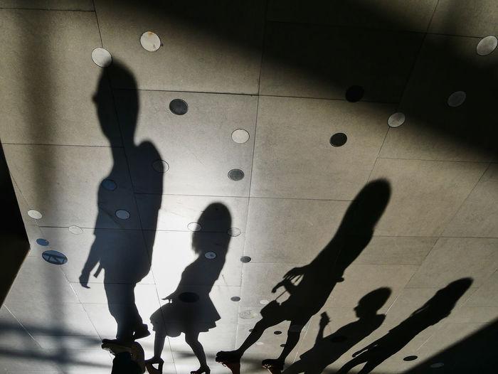 Shadow of people walking on tiled floor