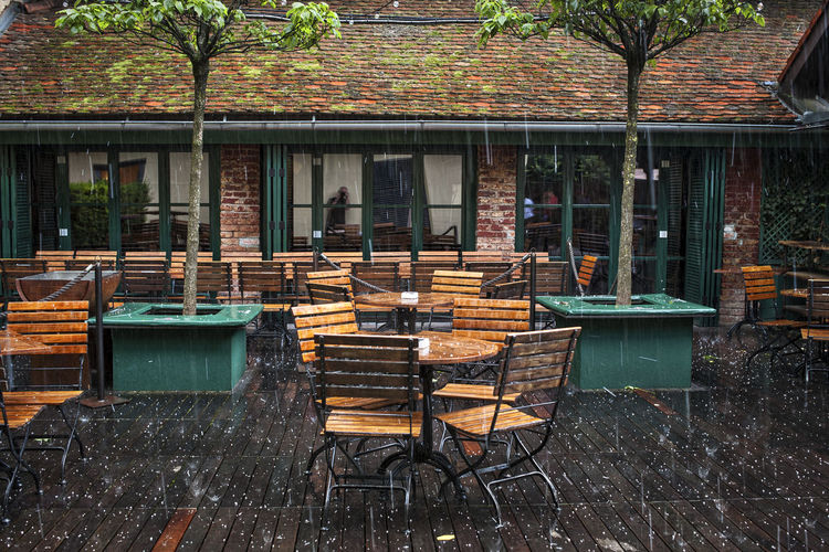 Empty chairs and tables at sidewalk cafe against building