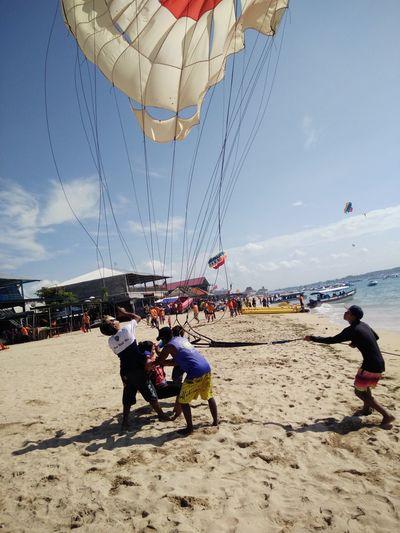 Beach Casual Clothing Day Enjoyment Full Length Fun Leisure Activity Lifestyles Mixed Age Range Outdoors Parasol Sand Sea Shore Sky Summer Tourism Tourist Vacations Bali, Indonesia Tanjungbenoa Nusadua Watersports Parasailing