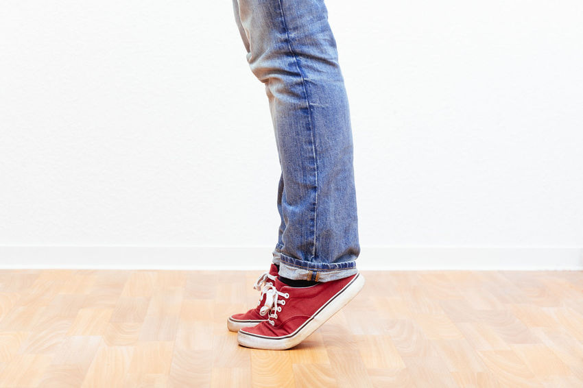 Man on tip toes, anonymous bottom half crop, indoors studio people shot. Balance Casual Clothing Human Body Part Jeans Lifestyles Low Section Men Real People Standing Standing Stretching Tip Toe Toes Upward
