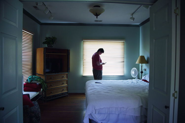 Woman using smart phone while standing against window in bedroom