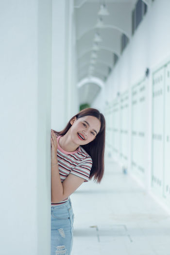 Portrait of smiling young woman standing in corridor