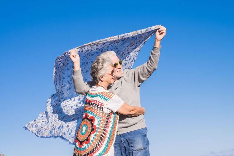 Senior Couple Holding Scarf Against Clear Blue Sky