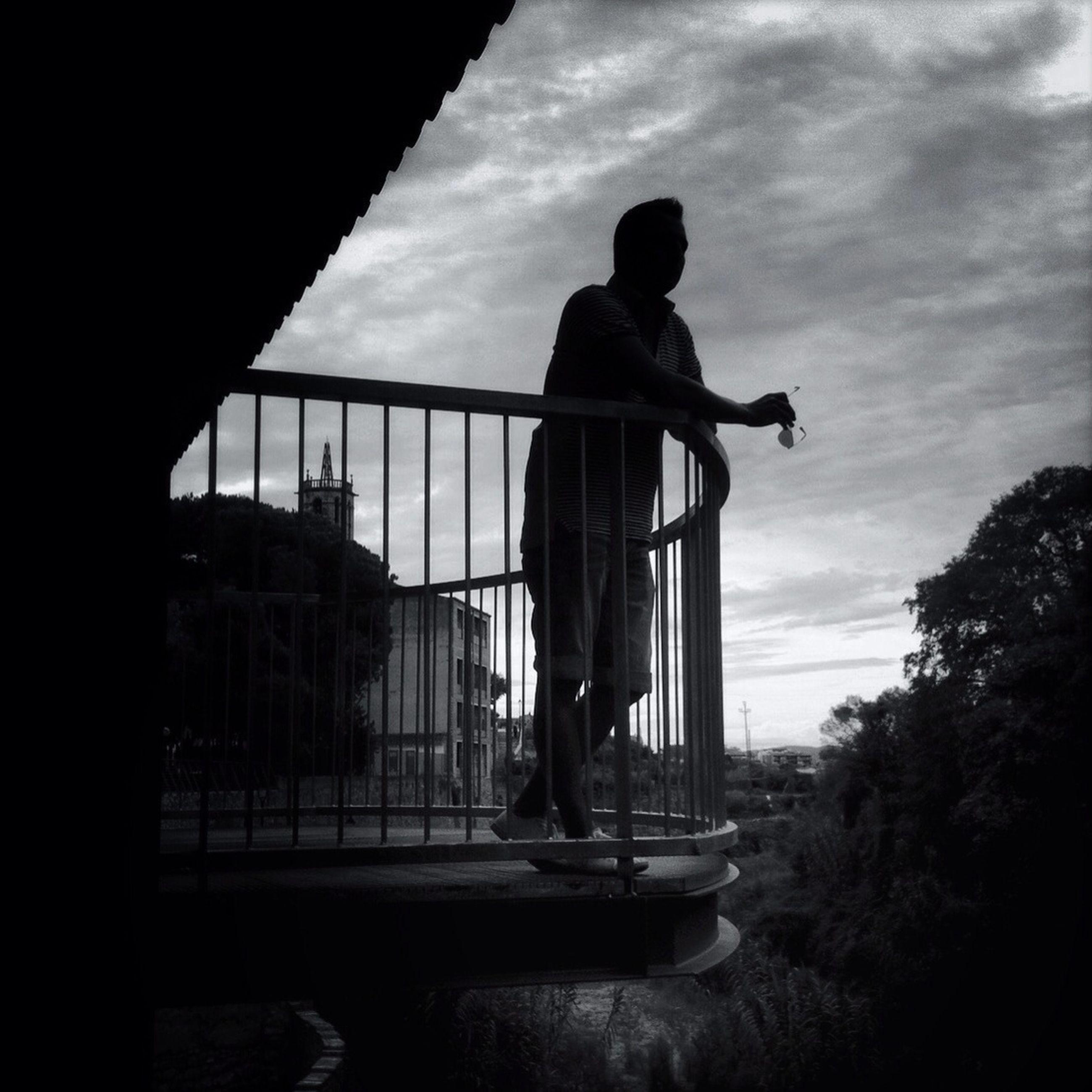 silhouette, sky, full length, lifestyles, men, leisure activity, standing, rear view, built structure, cloud - sky, architecture, side view, person, transportation, cloud, railing, sunset