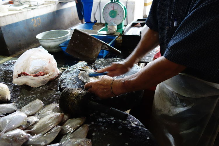 Midsection Of Man Cleaning Fish At Market