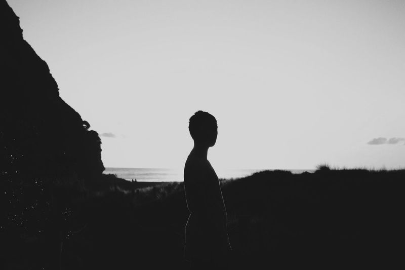 Silhouette woman standing on landscape against clear sky