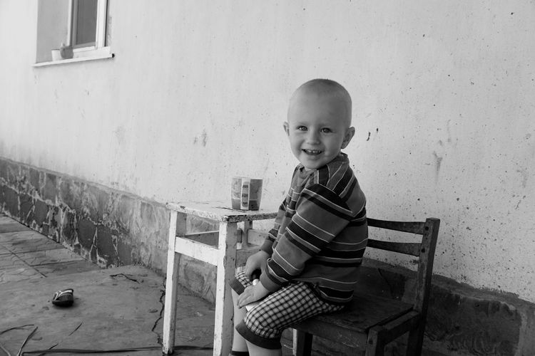 Portrait of boy smiling while sitting at table against wall