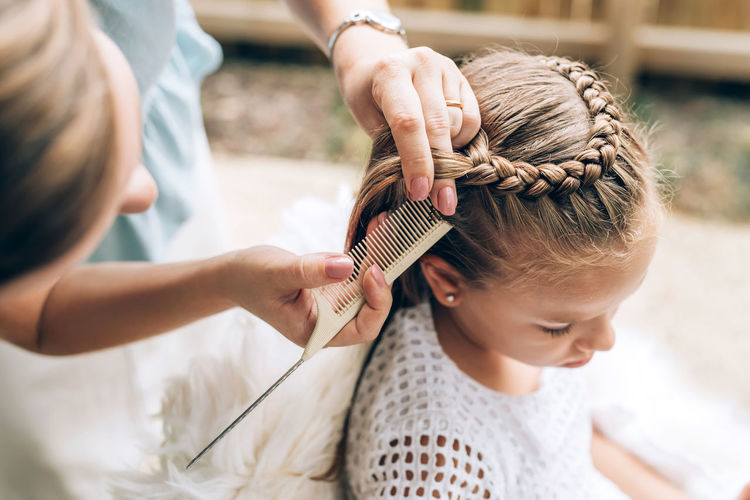 High angle view of woman hairstyling daughter