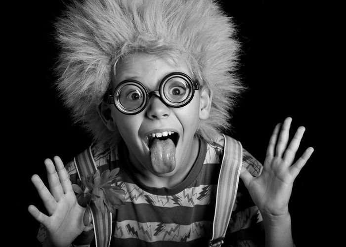 Wacky, zany , nutty child .clown ,boy in clown wig, suspenders and crazy glasses Studio Shot Portrait Front View Headshot One Person Child Childhood Mouth Open Mouth Black Background Males  Men Emotion Facial Expression Fun Close-up Innocence Sillouette Goofy Zany Wacky Weird Boy Suspenders Geek Crazy Nuts Odd Ball . Clown Actor Dress Up Costume Black And White Tounge Out  Fooling Around Foolish Unusual