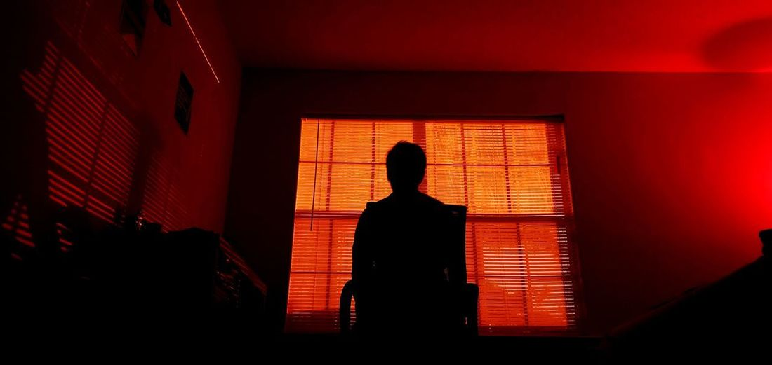 Rear view of silhouette man standing in illuminated building