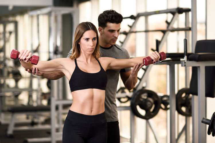 Trainer Assisting Woman Exercising In Gym