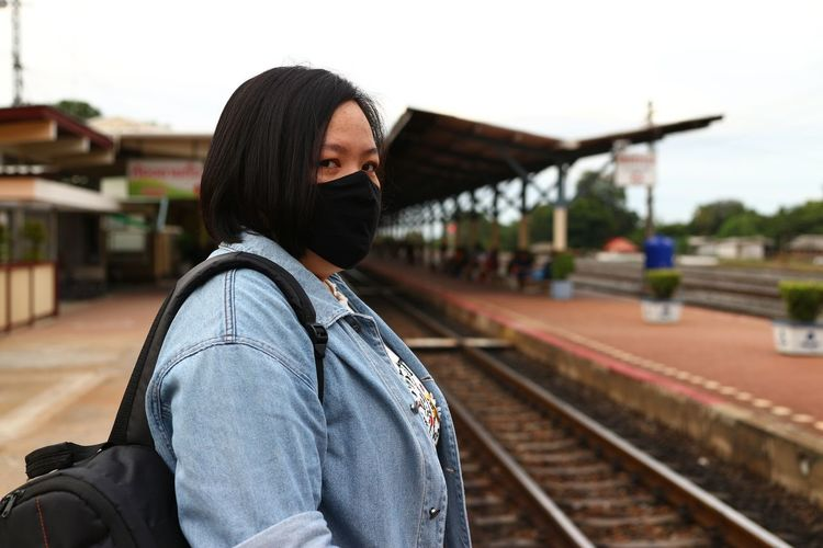 Woman wearing mask standing on railroad station platform