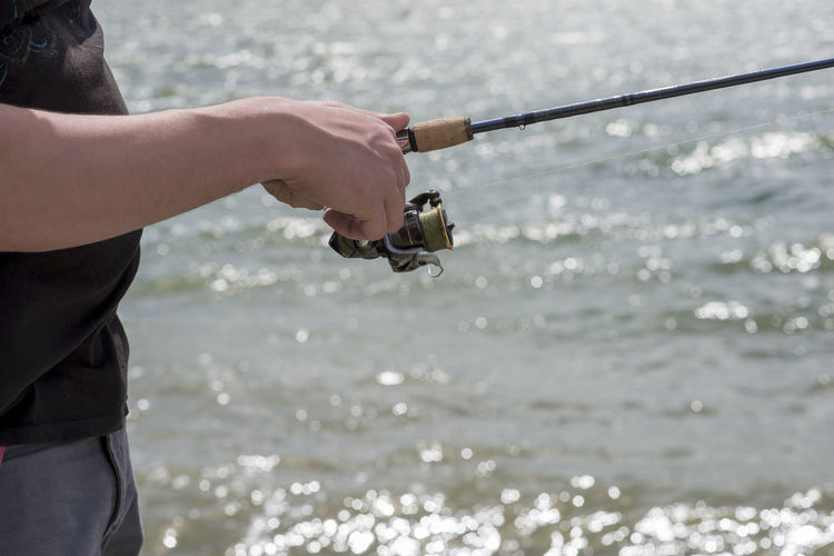 Midsection of man fishing in sea