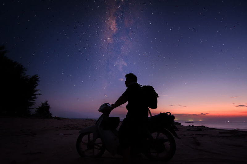 Silhouette man riding motorcycle against sky at night
